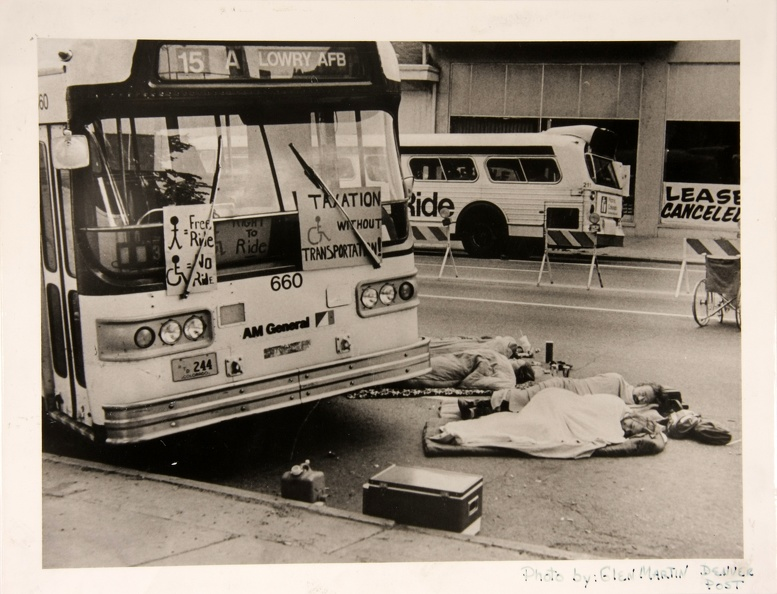 Four men and women are lying wrapped in sleeping bags or blankets on pads in the street in front of a bus. The bus _15 A_ once bound for Lowry AFB_ now appears empty and on the front are 3 handmade posters. Two are outside under the windshield wipers. One says _Taxation without Transportation__ with a drawing of the access symbol_ the other has a picture of a stick figure person next to an equals sign and the words Free Ride_ and then an access symbol guy next to an equals sign and the words No Ride. Inside the window a third sign is partially visible with the access symbol and the words Right to Ride.   There are police_traffic barriers down the middle of the street and a manual wheelchair. There is a bus parked on the opposite side of the street and behind it a city building with a big sign that says _lease canceled._   Around the people lying down are small piles of stuff and there is a cooler by the curb.